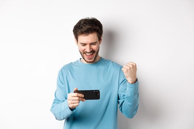 Gelukkig jongeman winnen in videogame op smartphone, mobiel scherm kijken en ja zeggen, maken vuist pomp in viering, online doel bereiken, staande op witte achtergrond.