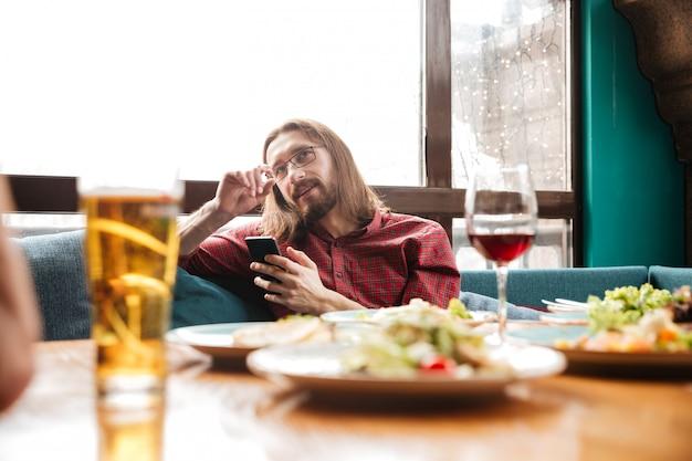 Gelukkig jongeman zittend in café tijdens het gebruik van mobiele telefoon