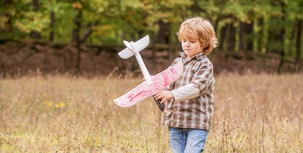 Gelukkig jongen speel vliegtuig. kleine jongen met vliegtuig. een klein kind droomt ervan piloot te worden.