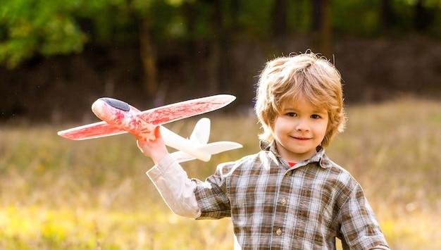 Gelukkig jongen speel vliegtuig. kleine jongen met vliegtuig. kind droomt ervan piloot te worden