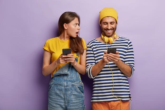 Gelukkig jongere leest berichten in sociale netwerken, draagt koptelefoon, gestreepte trui, houdt moderne mobiele telefoon, boze vrouw