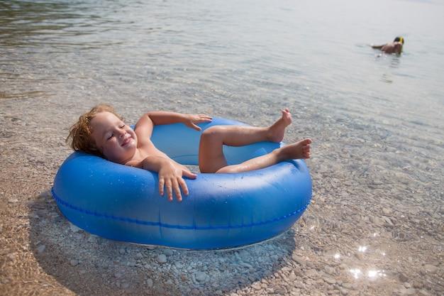 Gelukkig jongetje drijft op een opblaasbare ring in de zee