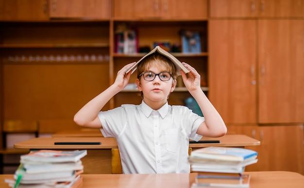 Gelukkig jongetje heeft idee. schooltaak doen met veel boeken.