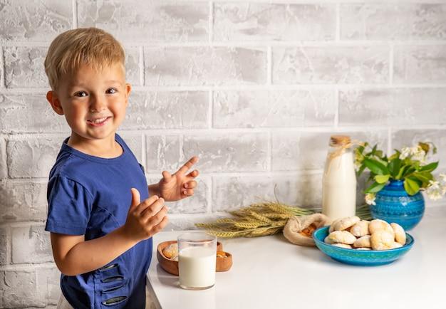 Gelukkig jongetje in een blauw t-shirt drinkt melk en eet koekjes op een lichte achtergrond
