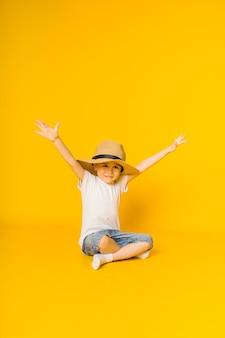 Gelukkig jongetje in een strooien hoed zit op een gele ondergrond met ruimte voor tekst