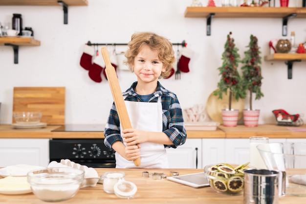 Gelukkig jongetje in schort met deegroller terwijl hij koekjes gaat maken in de keuken om zijn moeder te helpen