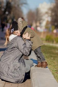 Gelukkig jongetje kussen moeder buitenshuis. moederdag