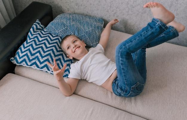Gelukkig jongetje ligt op de bank op zijn rug met zijn benen omhoog en lacht