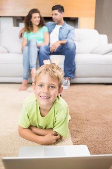 Gelukkig jongetje met behulp van laptop op het tapijt met ouders zitten bank