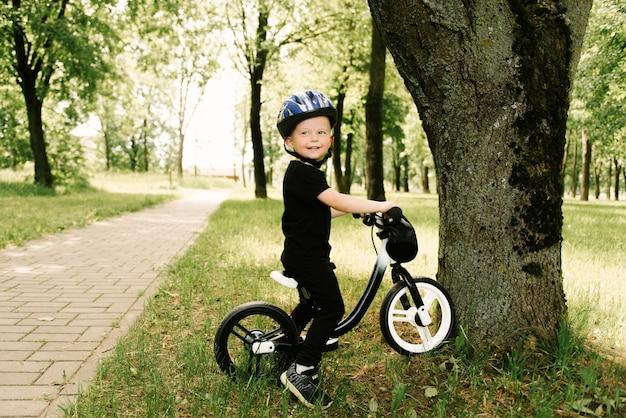 Gelukkig jongetje met een fiets die in het park loopt