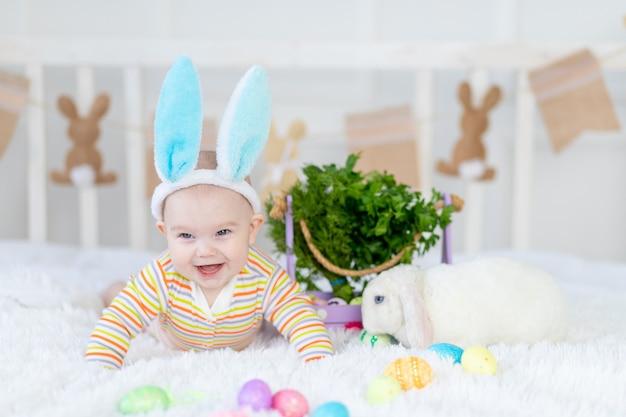 Gelukkig jongetje met konijnenoren op zijn hoofd liggend met een konijn op het bed met paaseieren, schattige grappige lachende kleine baby. het concept van pasen.