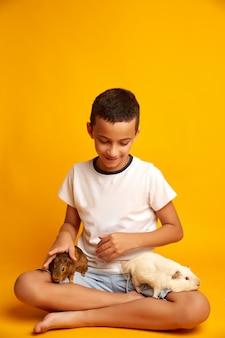 Gelukkig jongetje met schattige cavia's. optimistische jongen die en aanbiddelijke proefkonijnen glimlachen bekijken tegen Premium Foto