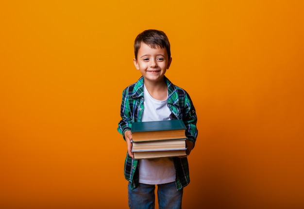 Gelukkig jongetje met zware boeken geïsoleerd gele achtergrond. onderwijsconcept