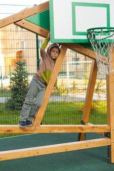 Gelukkig jongetje op de speelplaats overdag. leuke buitenspellen. kinder ontwikkeling. een 6-7-jarige jongen speelt op straat