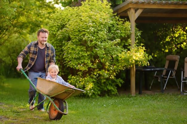 Gelukkig jongetje plezier in een kruiwagen duwen door papa in binnenlandse tuin op warme zonnige dag.