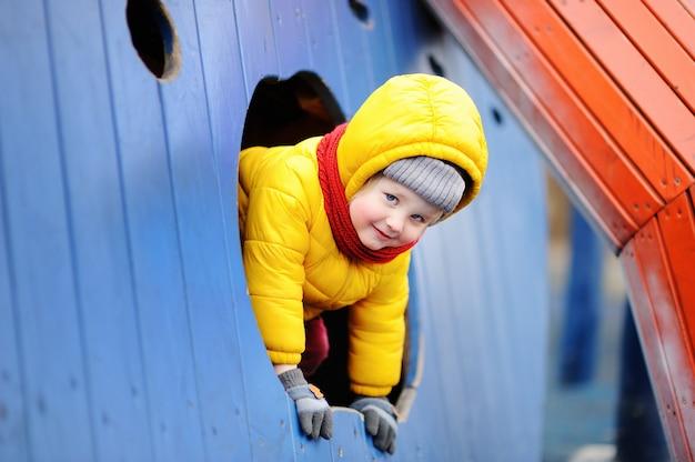 Gelukkig jongetje plezier op buitenspeeltuin. lente en herfst actieve vrijetijdsbesteding voor kinderen.