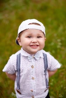 Gelukkig jongetje speelt in het gras in de zomer glimlachend met tanden en kijkt in de camera
