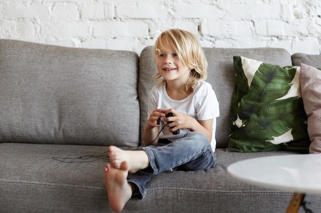 Gelukkig jongetje speelt spelletjes in de woonkamer