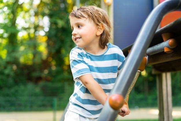 Gelukkig jongetje spelen in een park op speelplaats. peuter die wegkijkt en een glijbaan beklimt. zomeractiviteiten voor kinderen.