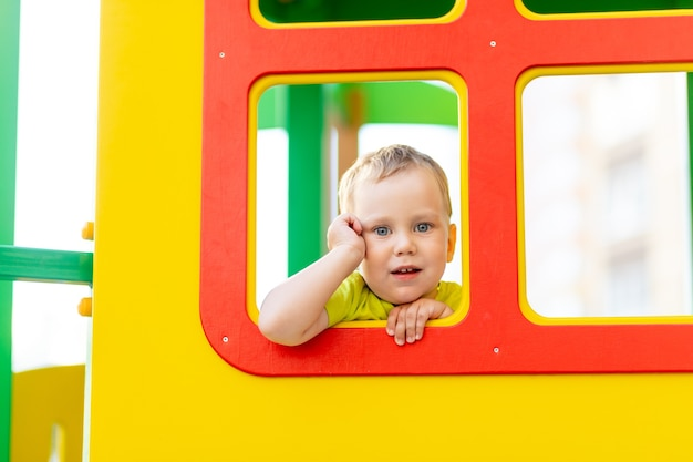 Gelukkig jongetje spelen op de speelplaats, jongen kijkt uit het raam, de levensstijl van kinderen