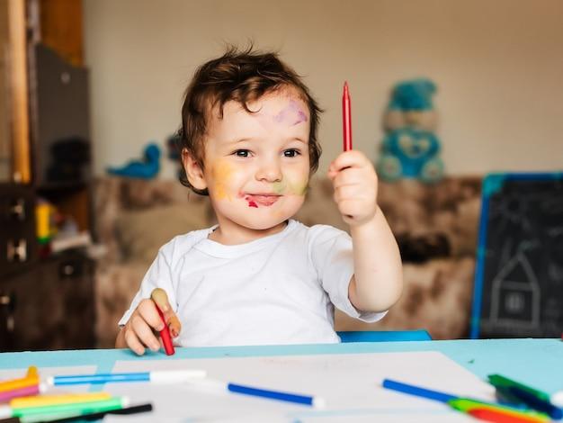 Gelukkig jongetje tekent met kleurrijke markeringen in een album