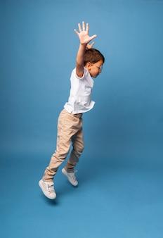 Gelukkig jongetje triomfantelijk met opgeheven handen op een blauwe achtergrond.