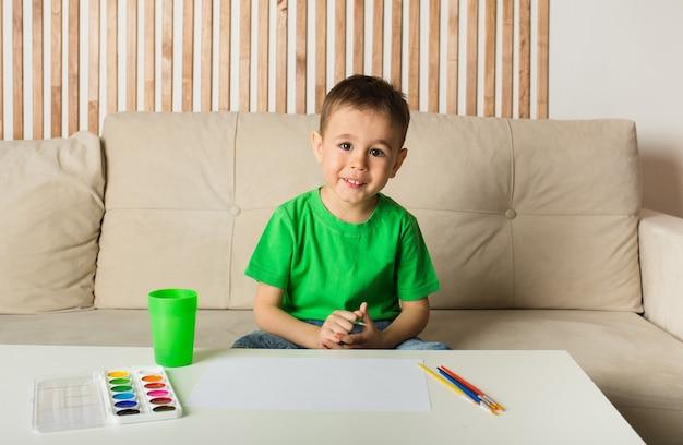 Gelukkig jongetje zit aan een tafel en tekent met een penseel en schildert op papier