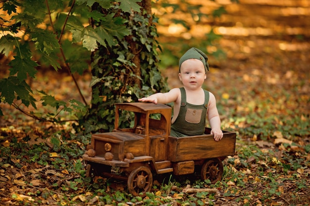 Gelukkig jongetje zit in de speelgoedauto van houten kinderen buiten in de zomer