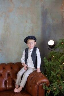Gelukkig jongetje zit op de bank in de buurt van de kerstboom