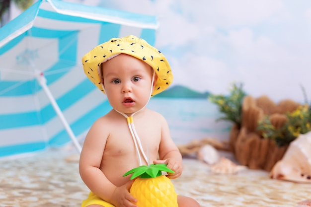Gelukkig jongetje zonnebaden op een zandstrand aan zee met palmbomen onder een parasol