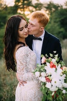 Gelukkig jonggehuwden kussen bij zonsondergang