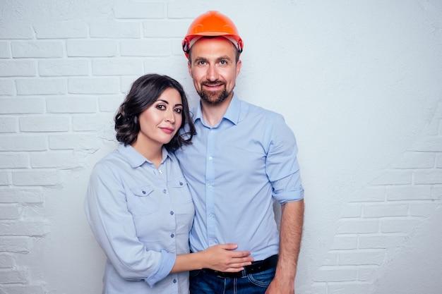 Gelukkig jonggehuwden mooie brunette vrouw en knappe man in een bouwhelm veiligheidshelm in een nieuw appartement witte bakstenen muur achtergrond.
