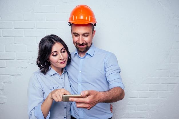 Gelukkig jonggehuwden mooie brunette vrouw en knappe man in een bouwhelm veiligheidshelm kijkend in de telefoon kiezen bouwmaterialen online aankoop.