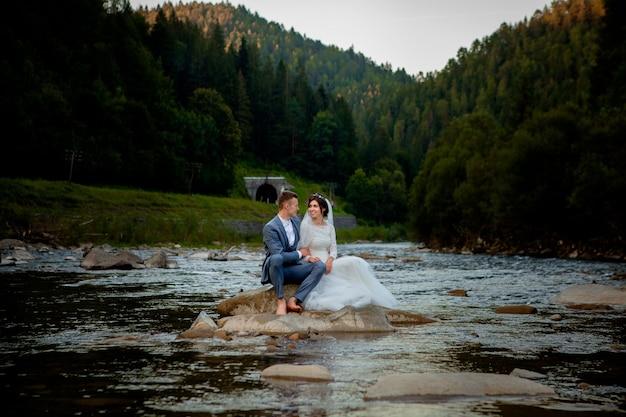 Gelukkig jonggehuwden permanent en lachend op de rivier. pasgetrouwden, foto voor valentijnsdag.