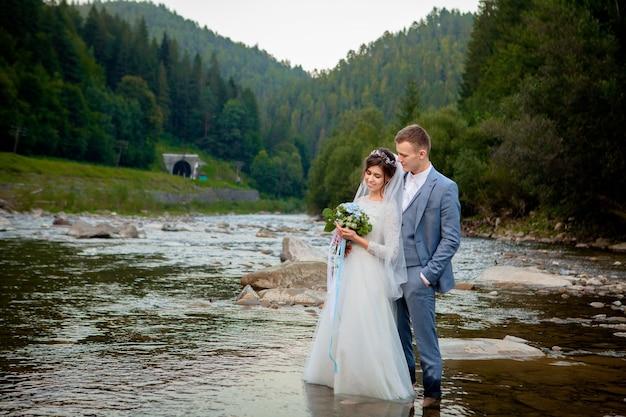 Gelukkig jonggehuwden permanent en lachend op de rivier