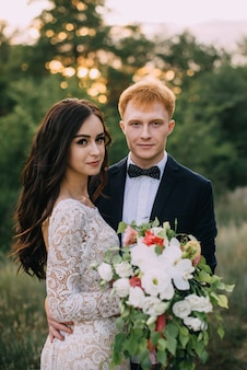 Gelukkig jonggehuwden staan en knuffelen op het pad, kijk naar de camera, close-up