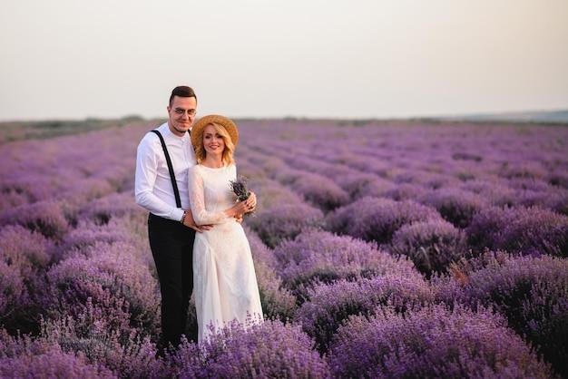 Gelukkig jonggehuwden staan in het bloeiende lavendelveld bij zonsopgang