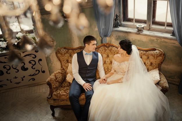 Gelukkig jonggehuwden zitten op de bank in een vintage interieur kijken elkaar hand in hand. mooi paar, man en vrouw, bruid en bruidegom. liefde, bruiloft concept.