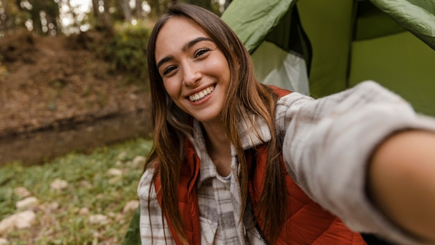 Gelukkig kamperend meisje in het bos dat een zelffoto neemt