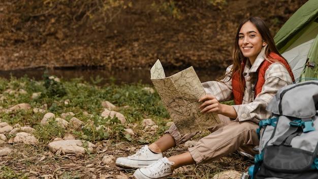 Gelukkig kamperend meisje in het bos die het lange schot van de kaart controleert