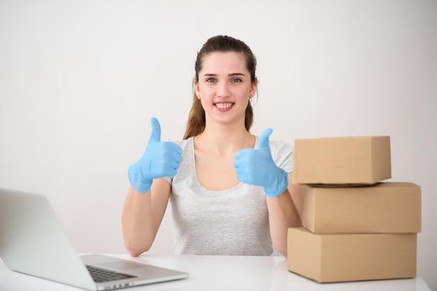 Gelukkig kantoormedewerker die het werk op het plaatsen van bestellingen op de computer heeft voltooid, toont goede handen met siliconenhandschoenen