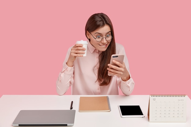 Gelukkig kantoormedewerker houdt mobiele telefoon, leest positief nieuws op webpagina terwijl internet bladert, trendy bril draagt, laptopcomputer, tablet heeft