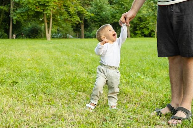 Gelukkig kaukasisch blond babymeisje dat op gras staat en naar een onherkenbare man kijkt, lacht, glimlacht. vader en kind wandelen in het park. vader en kind, samen tijd doorbrengen in de zomer. kopieer ruimte voor tekst.