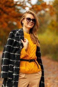 Gelukkig kaukasisch mooi meisje met schattige glimlach in gele vintage gebreide trui en mode jas met zonnebril wandelingen en rust buiten met kleurrijke herfstbladeren
