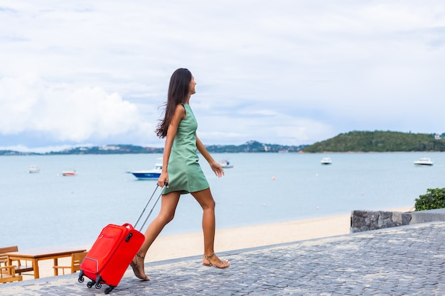 Gelukkig kaukasisch vrij lang haar elegante toeristische vrouw in jurk met rode koffer buiten hotel