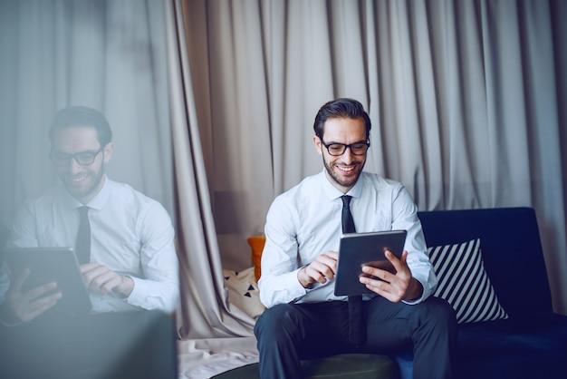 Gelukkig kaukasische bebaarde zakenman in stront en stropdas en met bril in zijn kantoor zitten en tablet gebruiken.