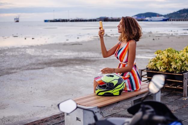 Gelukkig kaukasische biker vrouw in kleurrijke zomerjurk op vakantie met motorhelm