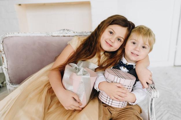 Gelukkig kaukasische broers en zussen knuffelen en bedrijf verpakt kerstcadeaus