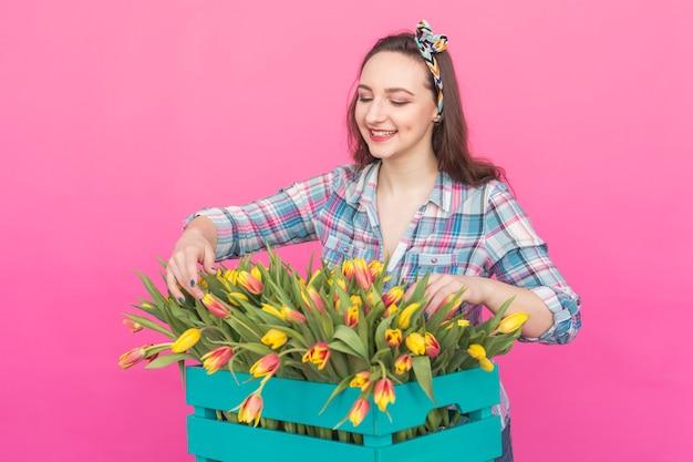 Gelukkig kaukasische jonge vrouw met doos gele tulpen op roze achtergrond