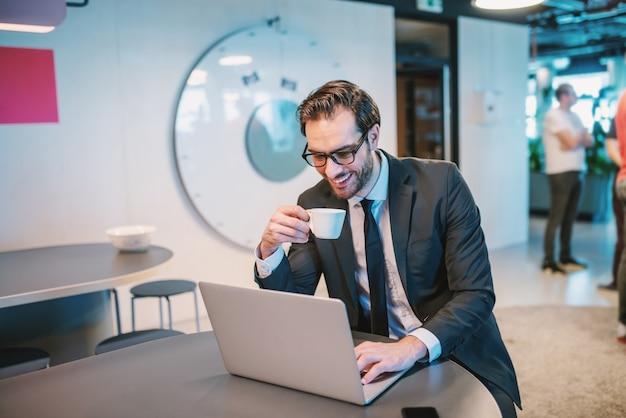 Gelukkig kaukasische knappe bebaarde zakenman in pak en met bril zit aan het aanrecht in gezelschap, koffie drinken en laptop gebruikt.